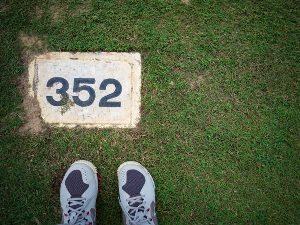 Yard label on the PAR 4 lady tee with lady golf shoes on green grass in a golf course stock photo