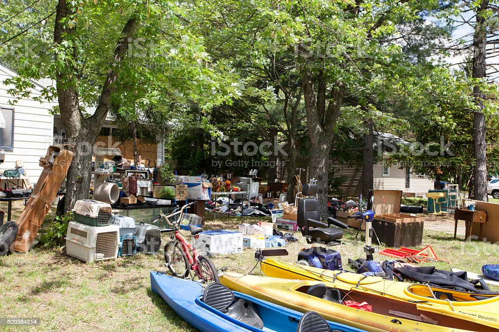 Yard sale in front yard of house with many items stock photo