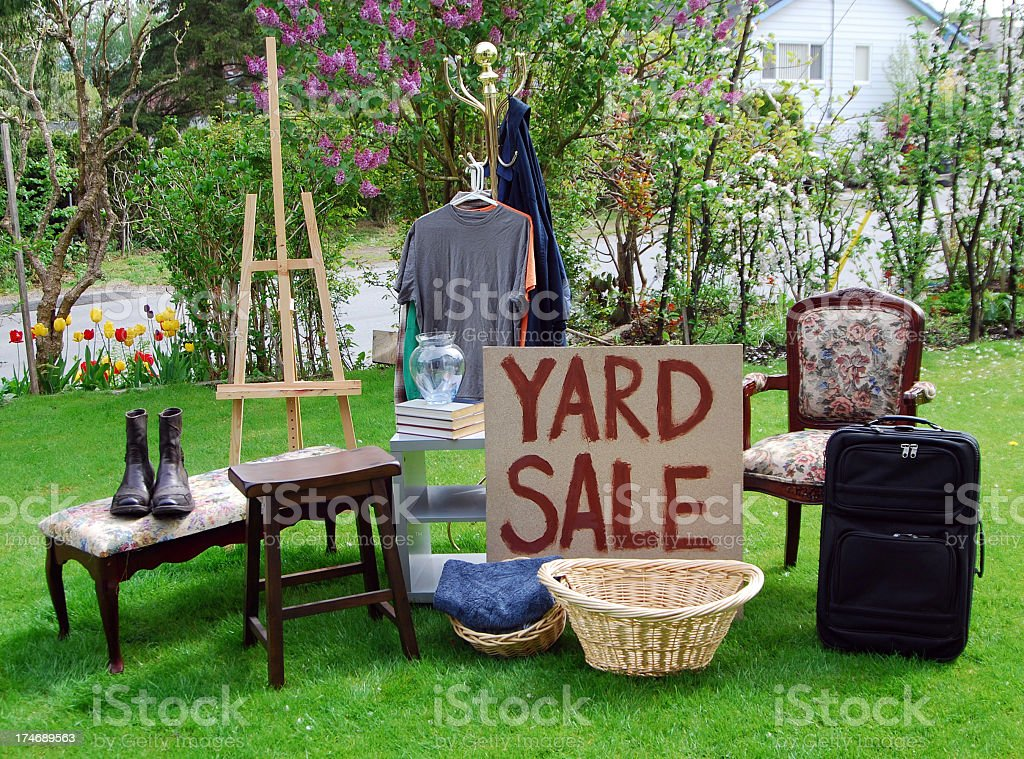 Yard sale sign on a lawn with various items stock photo