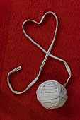 A red and white image of a crochet heart symbol. Ball yarn. Home, old times, background.