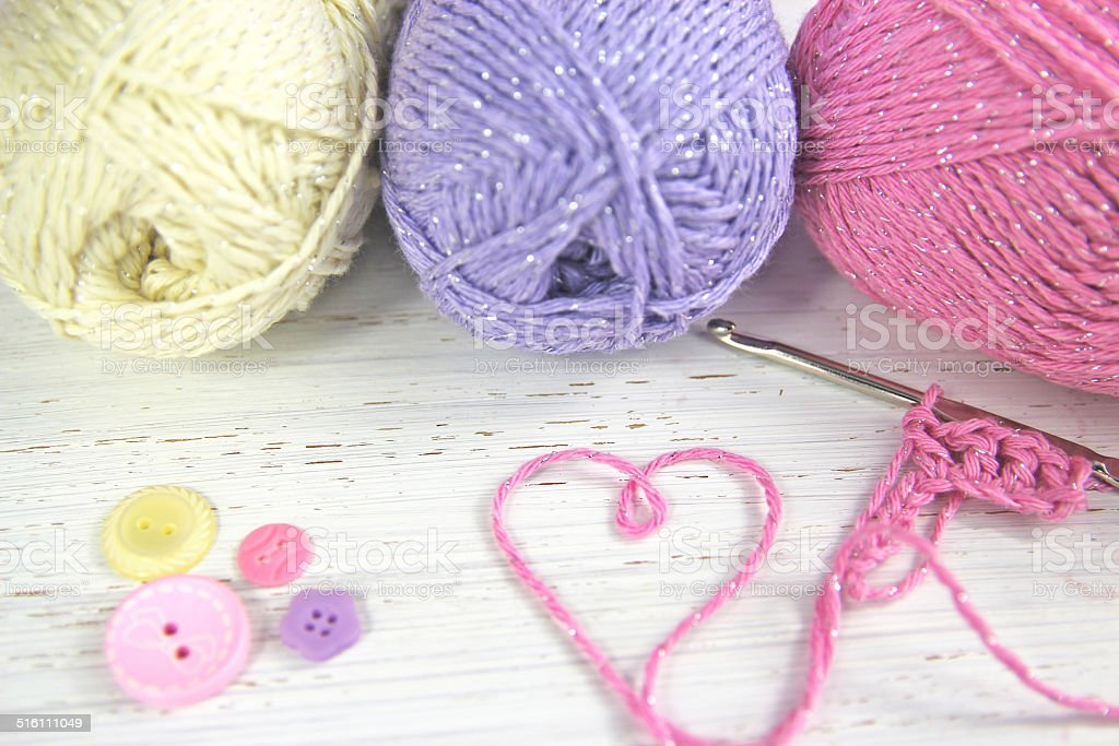 Yarn Wool pastel colours with crochet hook heart and buttons stock photo