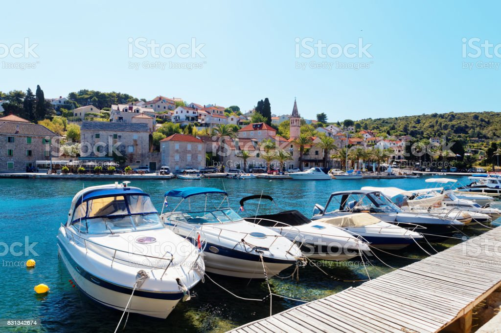 Yatchs and boats moored in the harbor of a small town Splitska - Croatia, island Brac stock photo