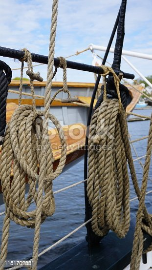 On the side of large sailing vessels are old yawl boats for quick transportation to and from marina docks when anchored.  These ropes add to the nautical view.