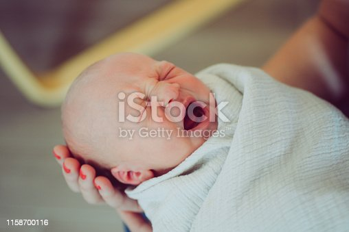Adorable newborn opens mouth to yawn or cry, being held by mom and wrapped in a cozy blanket. Child, infant, newborn and parenting lifestyle