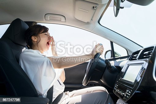 istock yawning female driver. falling asleep at the wheel concept. 867247798