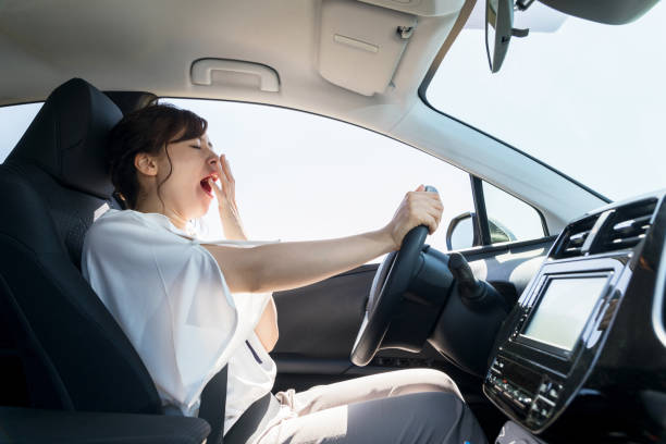 yawning female driver. falling asleep at the wheel concept. - driver stock photos and pictures