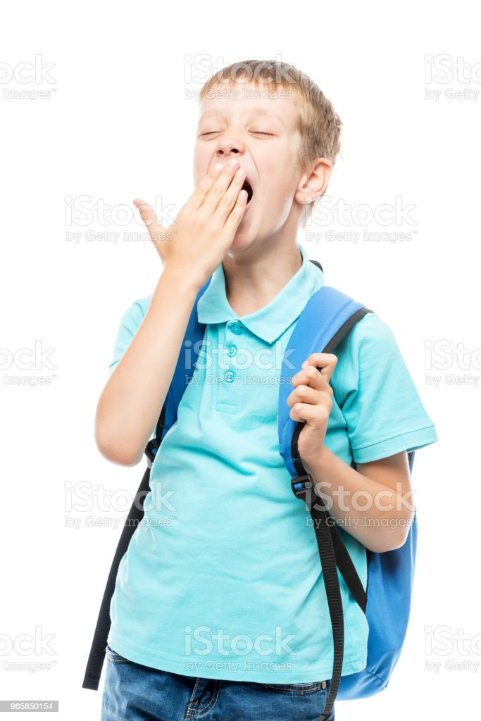 yawning schoolboy covers his mouth with his hand on a white background portrait isolated - Royalty-free Adolescence Stock Photo