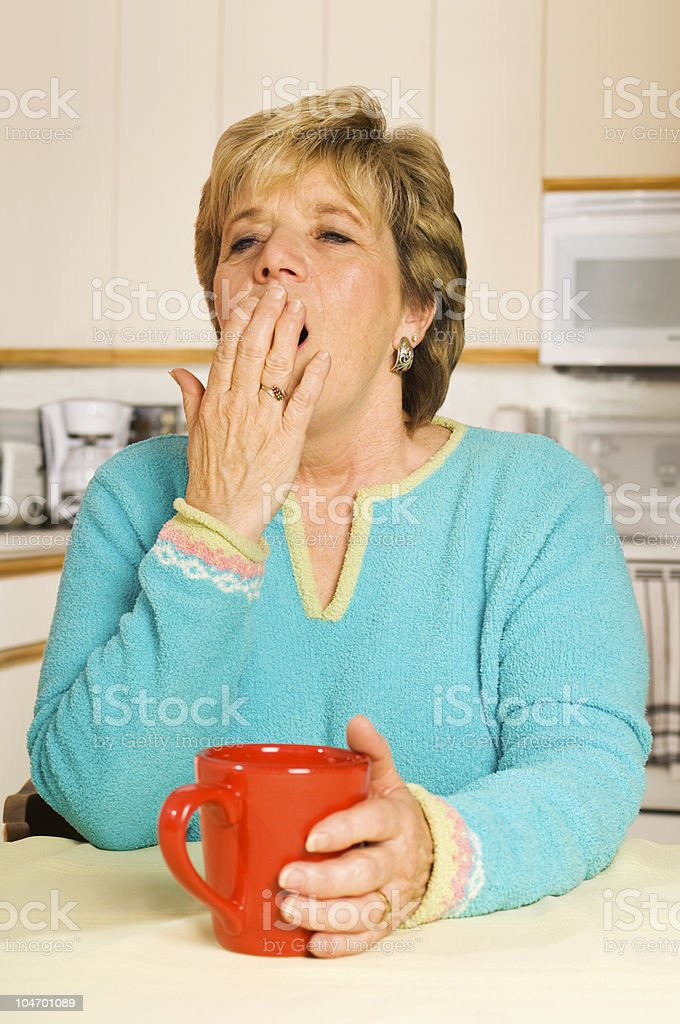 Yawning woman with red coffee mug in her kitchen royalty-free stock photo