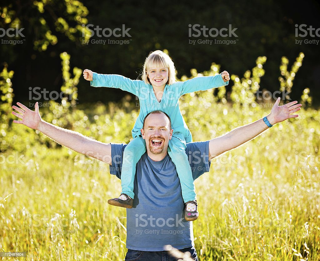 Yay! Delighted dad and daughter gesture playfully in field stock photo