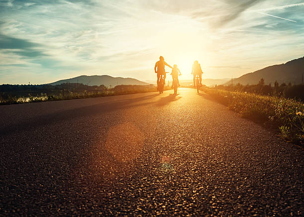 Сyclists family traveling on the road at sunset 스톡 사진