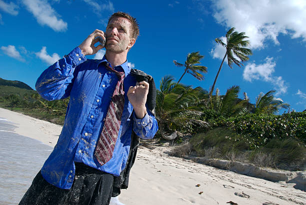 Yeah, I Flew Economy Businessman Stranded on Tropical Beach Wet and stranded businessman talks on his mobile phone on a deserted tropical island aground stock pictures, royalty-free photos & images