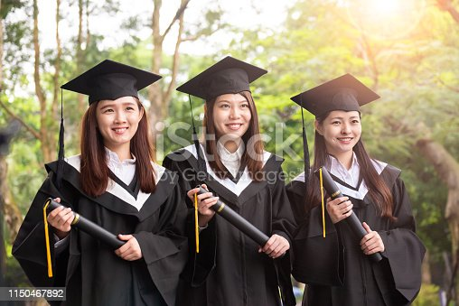 Three female university students with graduation gowns feeling excited and pride on their graduation day
