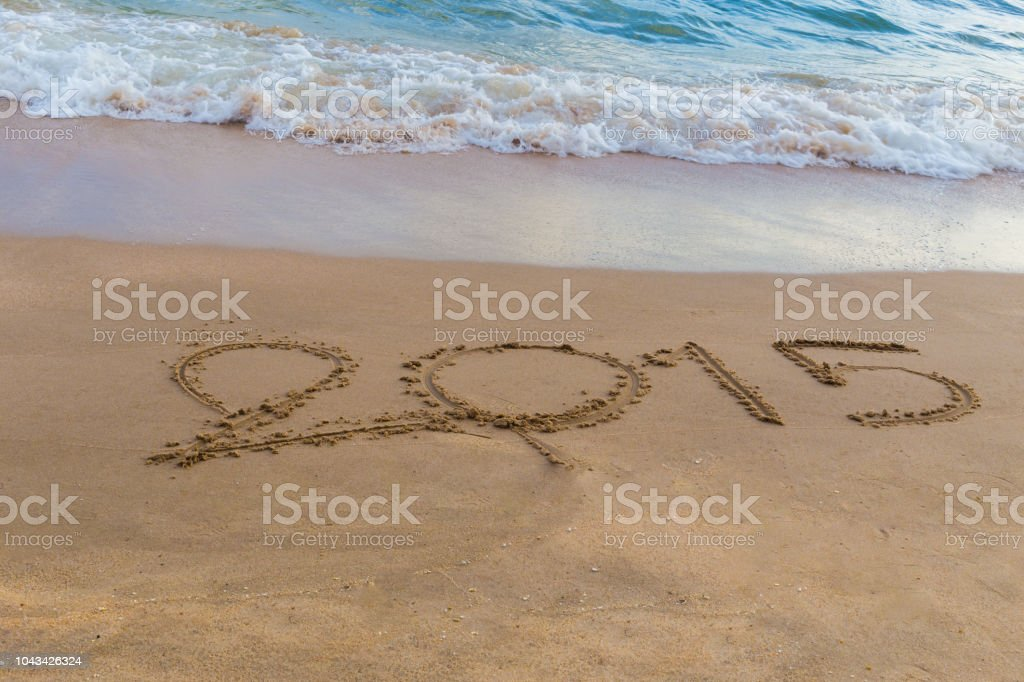 Year 2015 written in sand at the beach stock photo