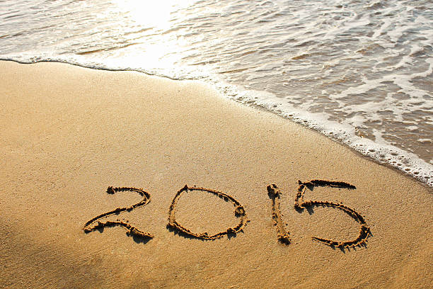 year 2015 written on sandy beach stock photo