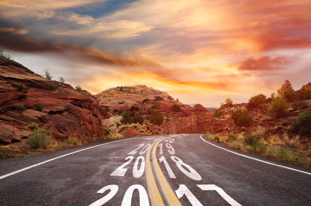 Year 2017 changing to 2018 - country road 2017-2018 road with sunrise 2017 stock pictures, royalty-free photos & images