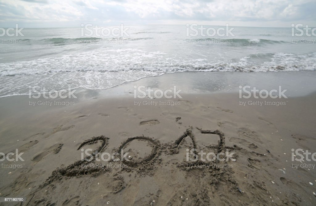 Year 2017 written on the sand of the sea waiting to be cleared b stock photo
