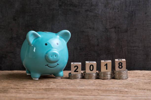 de financiële doel jaar 2018 met spaarvarken en stapel van munten en bovenop door houten kubus blok met nummer 2018 op tafel en een donkere zwarte achtergrond met kopie ruimte - 2018 stockfoto's en -beelden