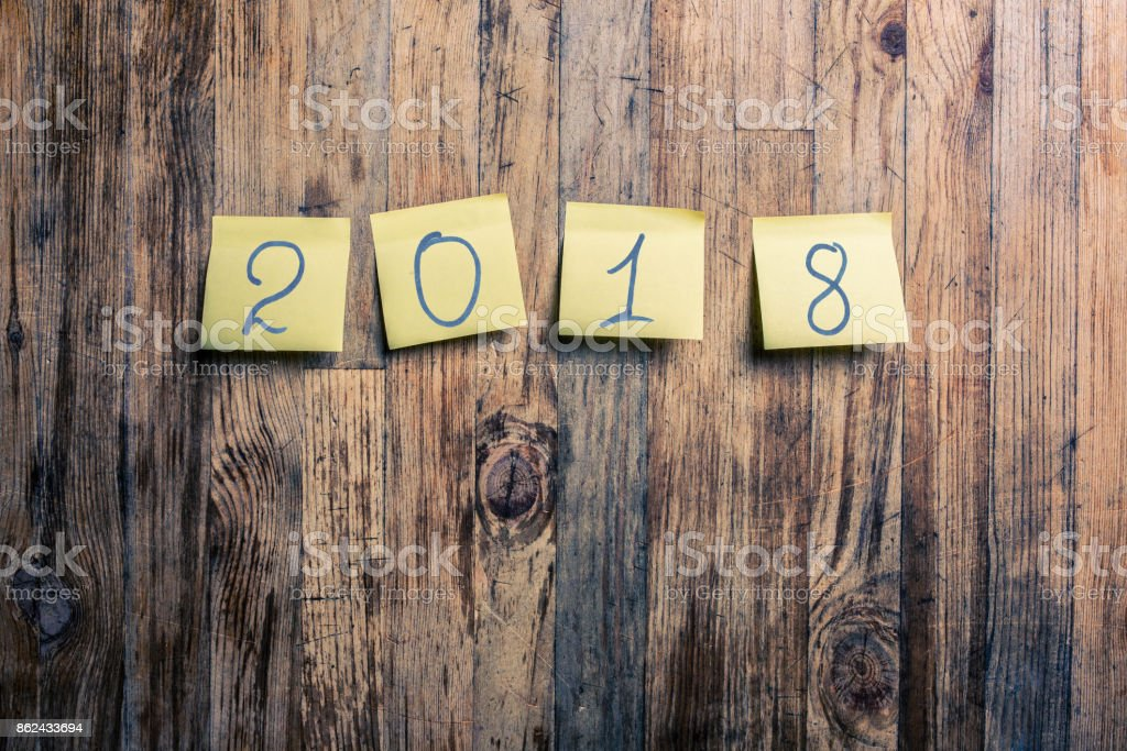 Year 2018 on postit notes attached to a wooden background stock photo