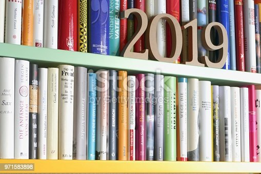 istock Year 2019 as wooden numbers standing on library shelf 971583898
