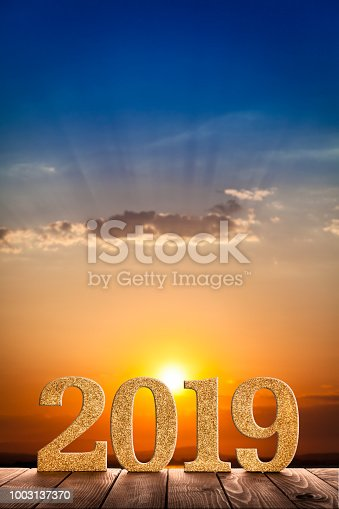 istock Year 2019 golden numbers on a wooden plank with sunrise/sunset at background 1003137370