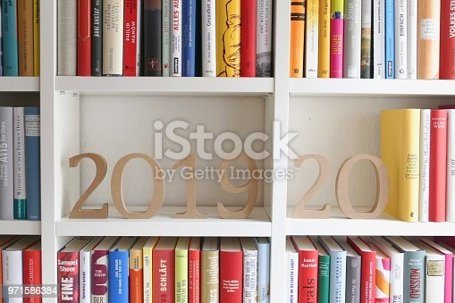 istock Year 2019/20 as wooden numbers standing on library shelf 971586384