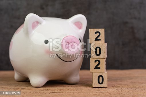 istock Year 2020 financial goal, savings, budget or investment, happy smiling pink piggy bank with stack of wooden cube blocks with number 2020 on table and dark black background 1166212789