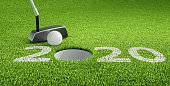 Golfball putting and the number 2020 on green grass