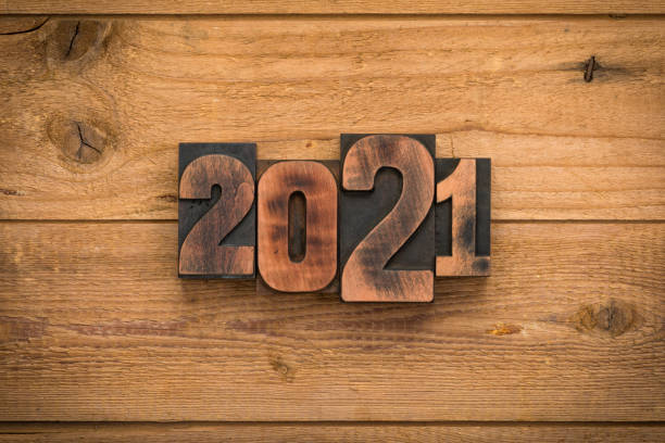 Year 2021, numbers written with vintage letterpress printing blocks on wood backgroiund stock photo