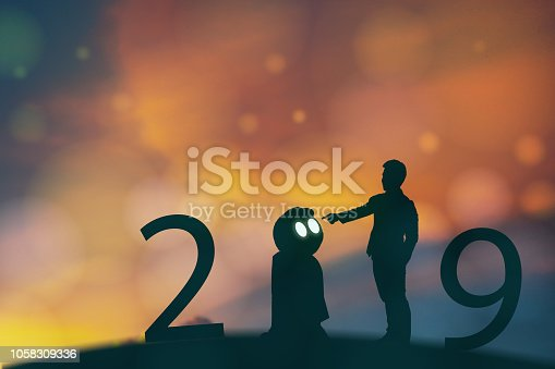 istock 2019 year artificial intelligence or ai futuristic concept, Silhouette  Business man stand and point hand to command or control assistant robot, industry 4.0 trend of automation robot in 2019 future 1058309336