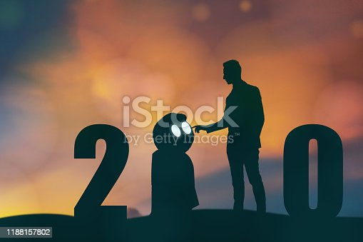 1042088340 istock photo 2020 year artificial intelligence or ai futuristic concept, Silhouette  Business man stand and point hand to command or control assistant robot, industry 4.0 trend of automation robot in 2020 future 1188157802