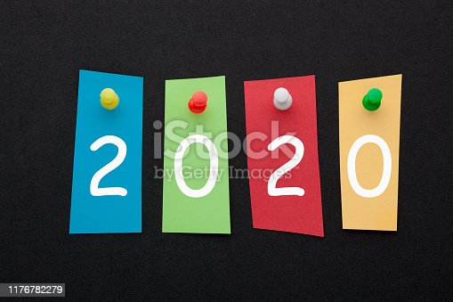 2020 written in colorful stickers pinned on black background. Business concept