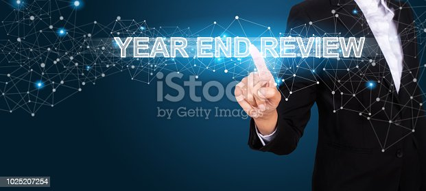 istock Year End Review concept with Hand of business pressing a button Year End Review. 1025207254