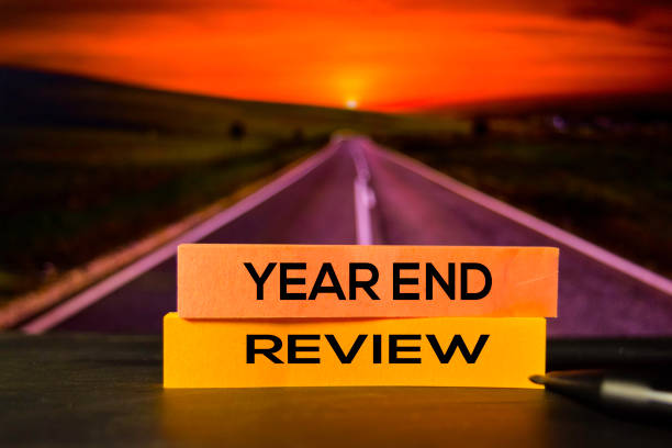 Year End Review on the sticky notes with bokeh background stock photo