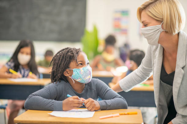6 year old, African American student wearing a protective face mask in class stock photo
