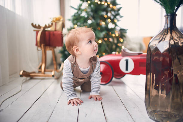 1 year old baby boy crawling on floor at home. christmas decorations on a background stock photo