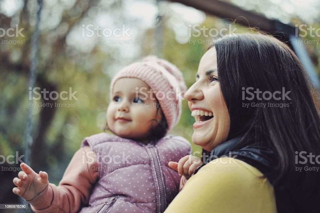 1 year old baby girl playing with her mom at a park stock photo