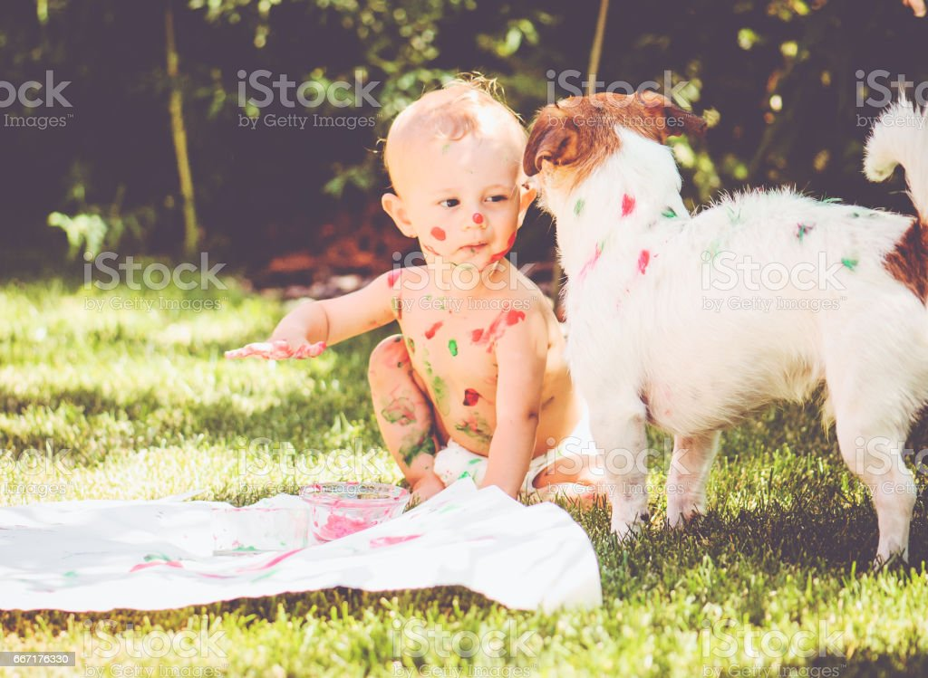 1 year old baby painting on his body and on dog stock photo