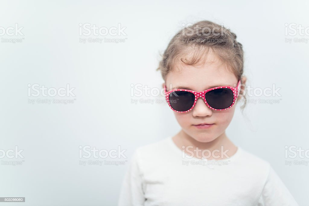 6 year old blond girl on white background whith sunglasses stock photo