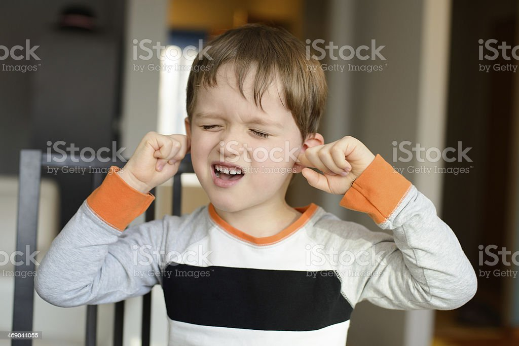 4 year old boy  clog his ears with fingers stock photo