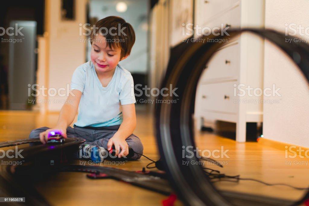 5 Jahre spielt alter Junge mit Slotcar Modell Rennstrecke – Foto