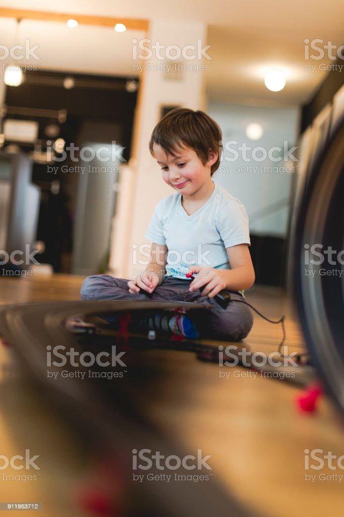 5 anos velho menino está jogando com pista de corrida de modelo de carro de slot - foto de acervo