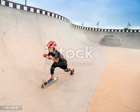 472091427istockphoto A 7 Year Old Boy On A Scooter At The Skate Park 1191487877