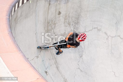 472091427 istock photo A 7 Year Old Boy On A Scooter At The Skate Park 1191487896