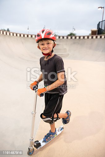 472091427istockphoto A 7 Year Old Boy On A Scooter At The Skate Park 1191487916