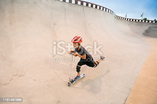 472091427 istock photo A 7 Year Old Boy On A Scooter At The Skate Park 1191487986