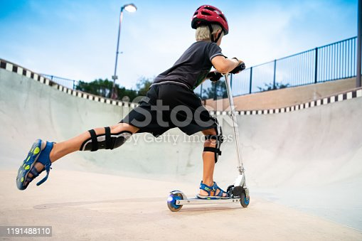 472091427 istock photo A 7 Year Old Boy On A Scooter At The Skate Park 1191488110