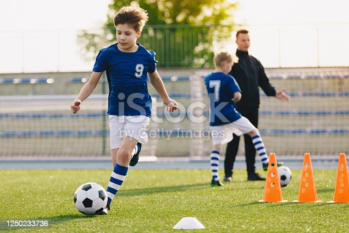 621475196 istock photo 10 year old boy running soccer ball. Elementary age school kids on football training with young coach. Children sports team improving dribbling speed and agility skills on session with training cones 1250233736