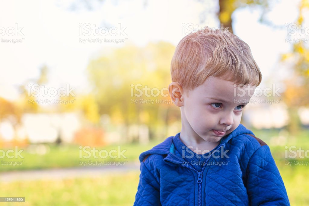 2 year old boy sulking in front of a camera stock photo