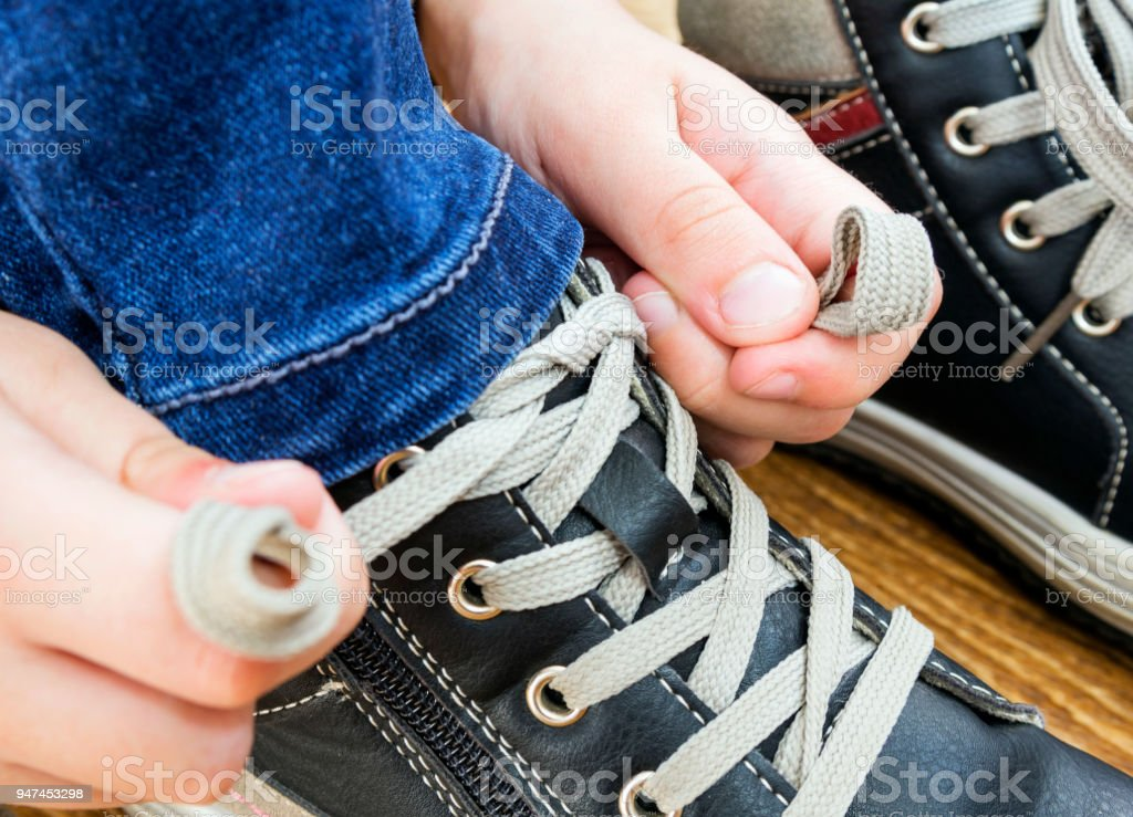 5 year old boy tying the laces on his walking shoes. Part of body,...