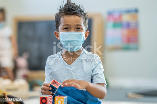 Mixed race boy playing at daycare while wearing a mask to protect from the transfer of germs during the COVID-19 outbreak.
